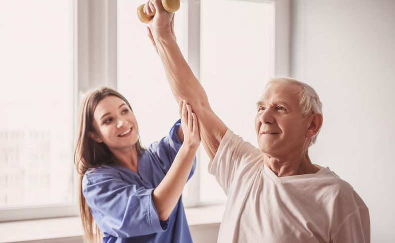 Handsome old man is doing exercises with dumbbells and smiling, in hospital ward. Attractive nurse is helping him
